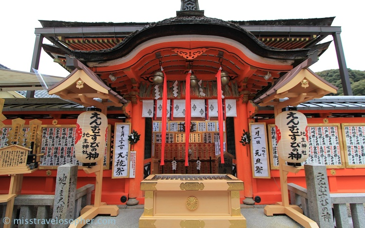 Main hall - offertory box in the foreground ; sashes/ropes hanging from the bells (Jishu Shrine or Love Shrine, Kyoto)